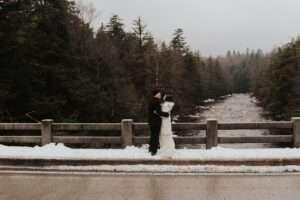 bride and groom on snowy bridge hugging