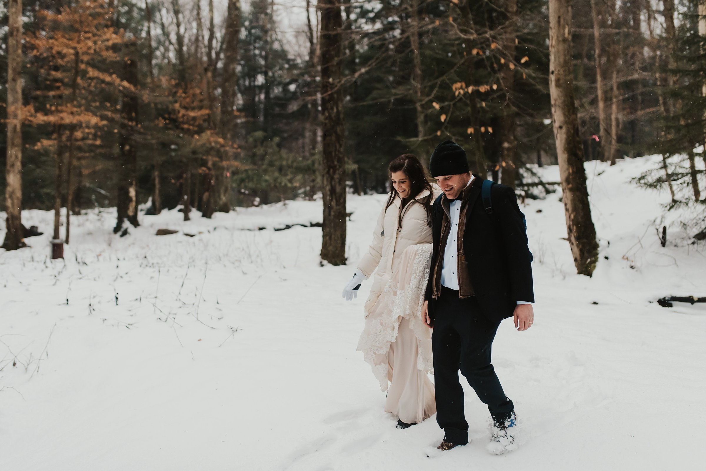 bride and groom hiking in snow on elopement day