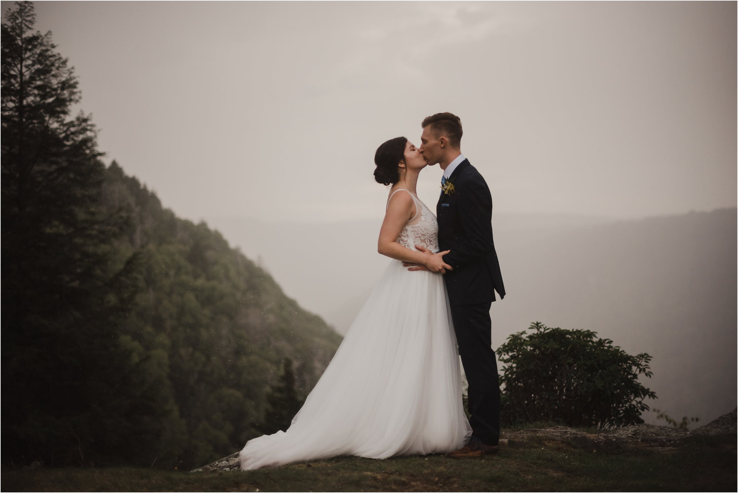 bride and groom kissing on mountain top at rainy and foggy wedding