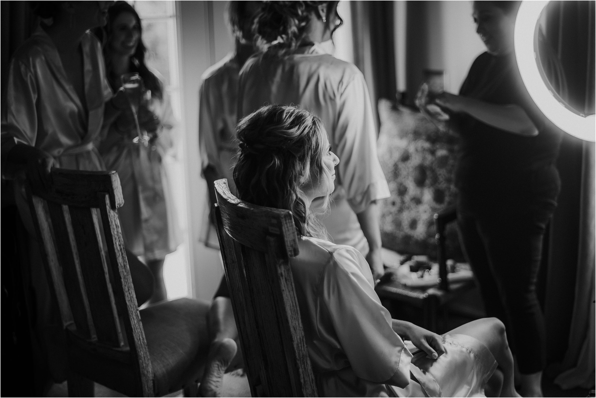 black and white image of bride getting ready with a ring light