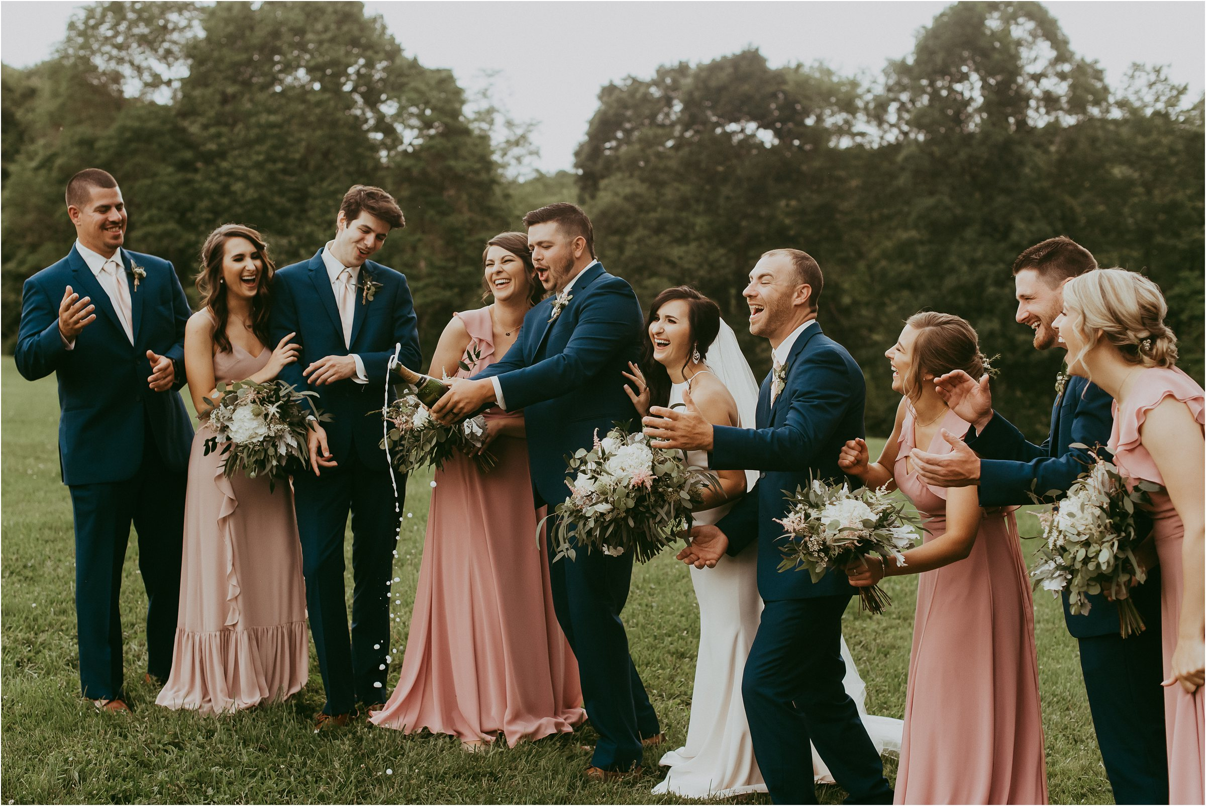 Bridal party popping champagne on mountain top at Maryland wedding