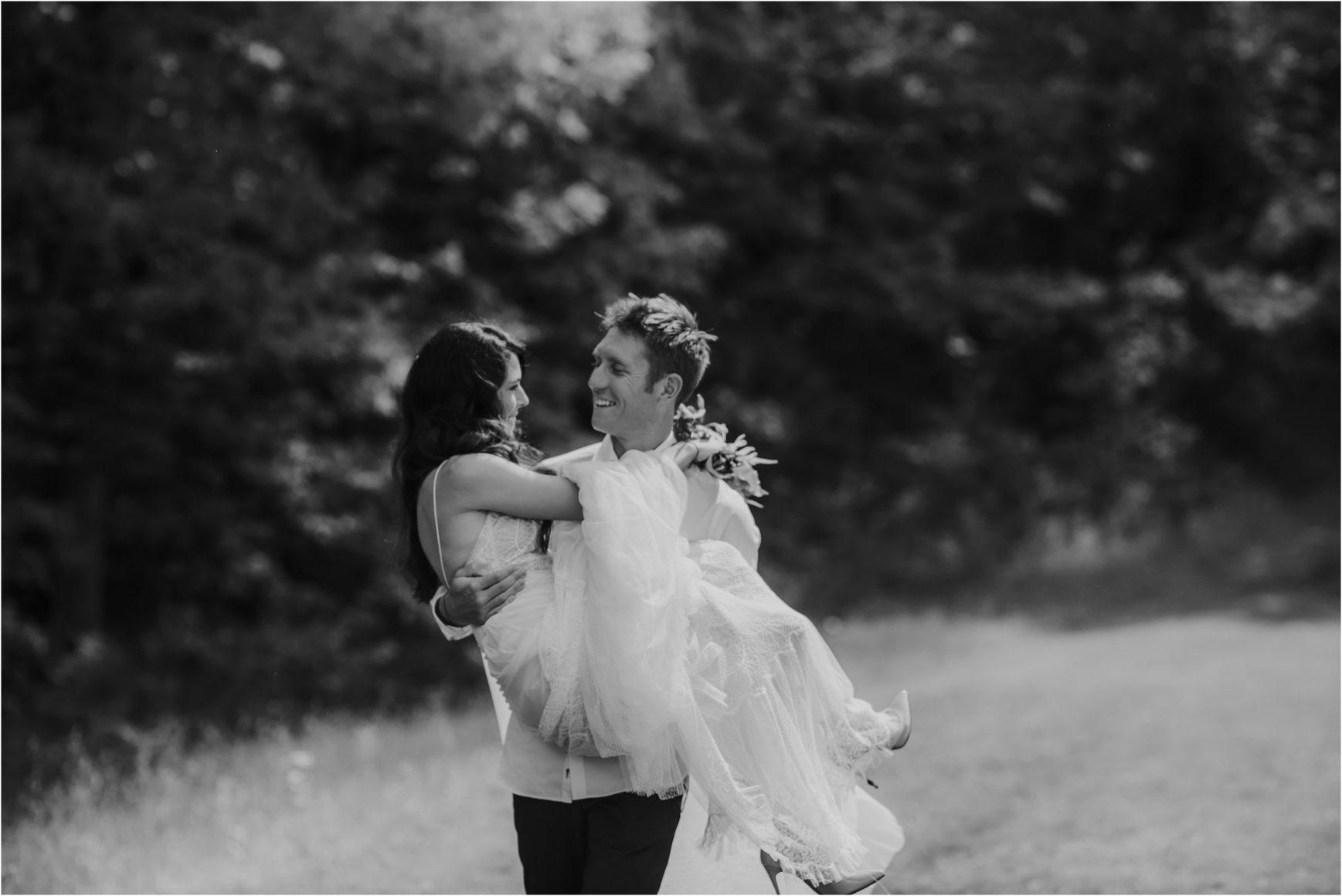 groom carrying bride in wedding dress during elopement