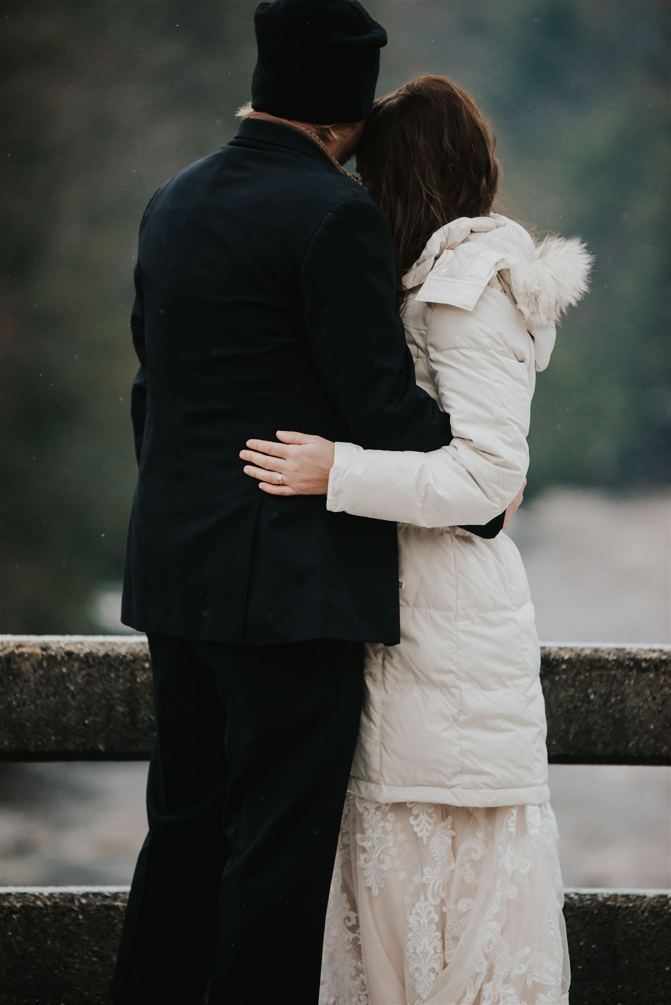 elopement couple hugging on a bridge in the snow
